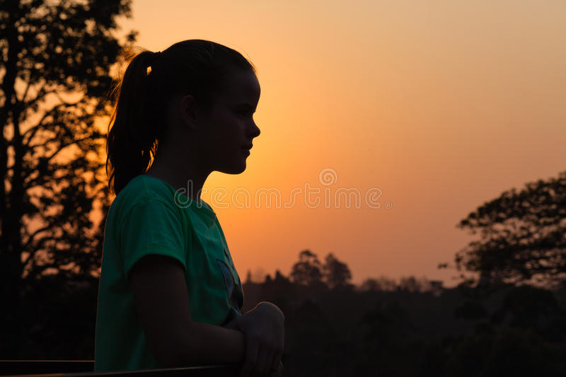 Girl Sunset Silhouette Contrast. Young girl watches sun setting going down silhouetted by colors of light royalty free stock photos