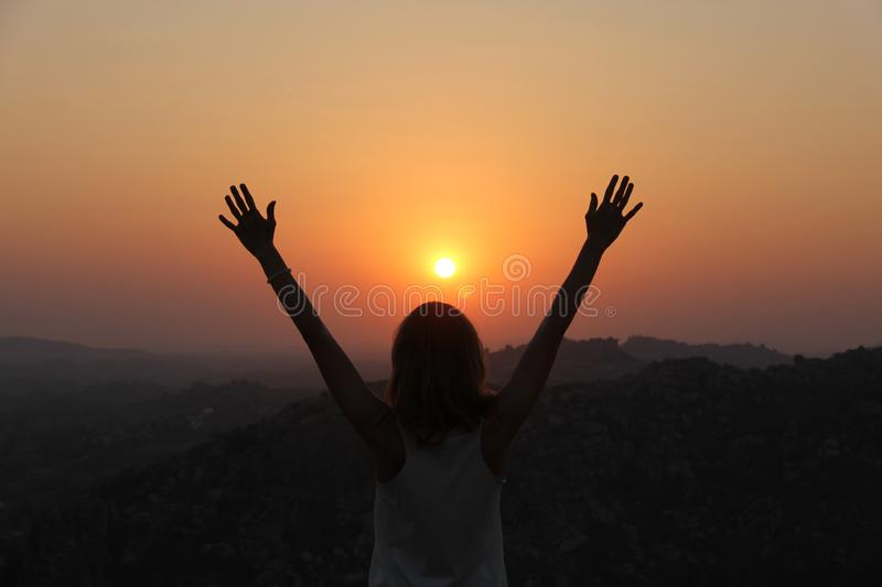 The girl at sunset. The girl stands with her back on the top of the mountain and looks at the sunset, welcomes the sun with her royalty free stock image