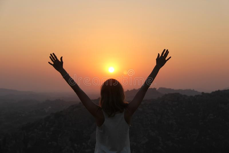 The girl at sunset. The girl stands with her back on the top of the mountain and looks at the sunset, welcomes the sun with her stock image