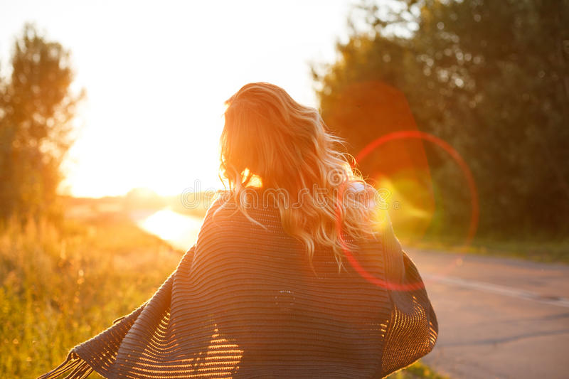 Girl and sunset. Young attractive girl is walking along the highway on a sunset background. The concept of traveling light stock images