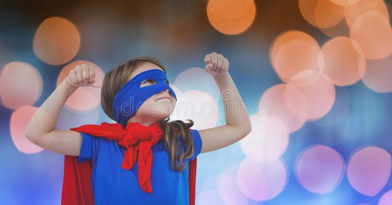 Girl in super hero costume over blur background royalty free stock photography