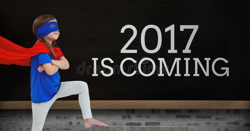Girl in superhero costume standing near a board with 2017 new year quotes. Girl in superhero costume standing near a black board with 2017 new year quotes royalty free stock images
