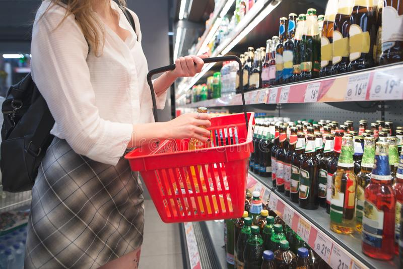 Girl is in the supermarket near the fridge with beer and puts the bottle in a red basket stock images