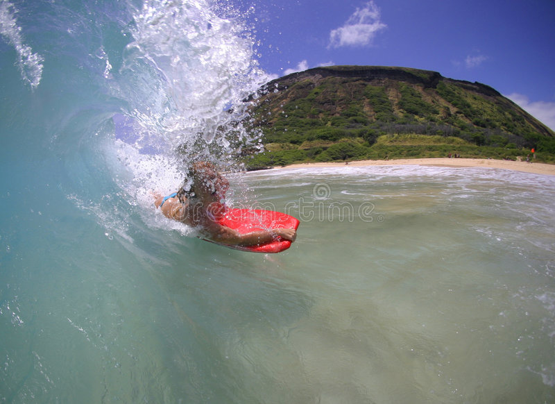 Girl Surfing a Big Wave in Hawaii. A teen girl rides a wave at Sandy Beach in Hawaii royalty free stock photography