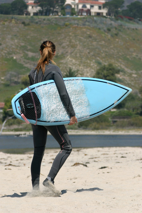 Girl with surfing board. Young girl with surfing board walking royalty free stock image