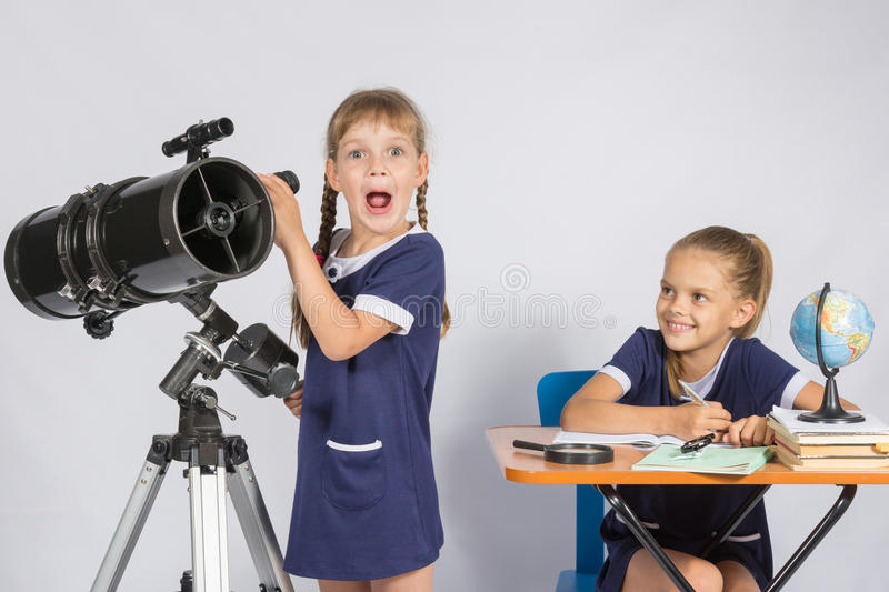 Girl surprised astronomer observing through a telescope, the other girl looked at her stock image
