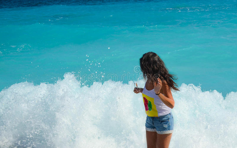Girl is surprised with the bubbly waves. Girl is standing in front of the sea waves, she is surprised with the bubbly foam. She is wearing short pants and white stock image