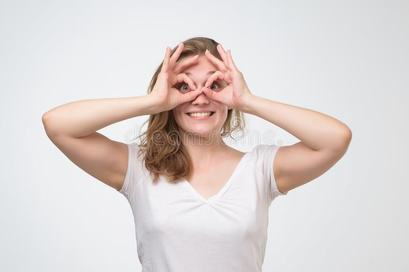 Girl with surprised face holding fingers in ok sign near eyes like glasses stock image