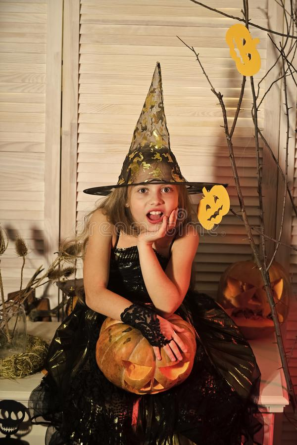 Girl with surprised face on spooky carnival room background. Halloween party and celebration concept. Little witch with Halloween decor. Kid in witch hat and royalty free stock photography