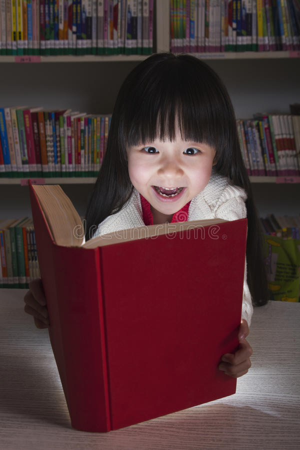 Girl Surprised By Glowing Book stock photo