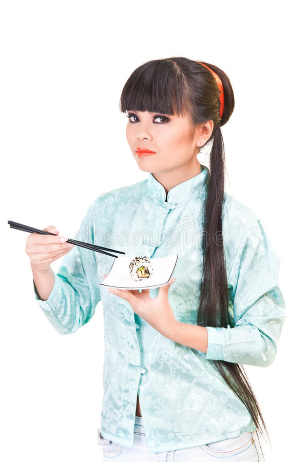 Girl and sushi. Young woman in east suit eating sushi royalty free stock images