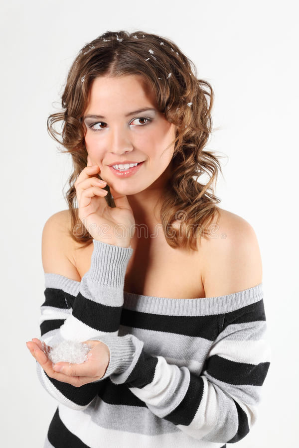 Girl in sweater with hair in snow holds snow in palm royalty free stock image