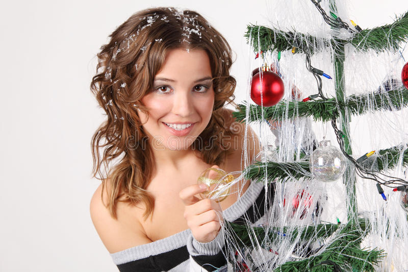Girl in sweater with hair in snow touches glass ball royalty free stock photos