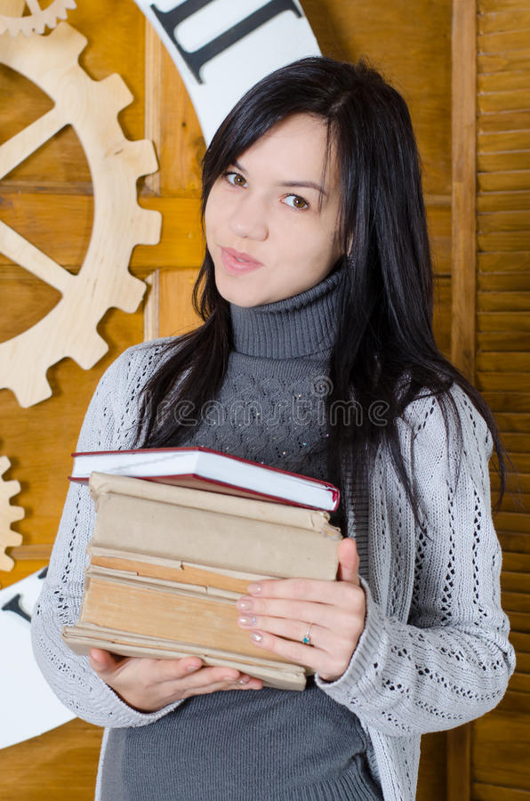 Girl in sweater holding books royalty free stock photos