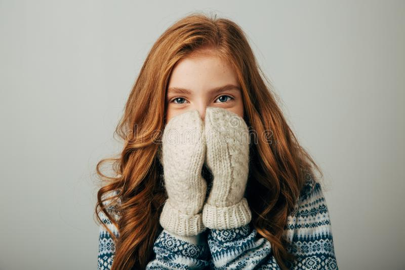 The girl in a sweater with red horns smiles, warming her face with gloves on her hands. Warm knitted gloves turned out royalty free stock images