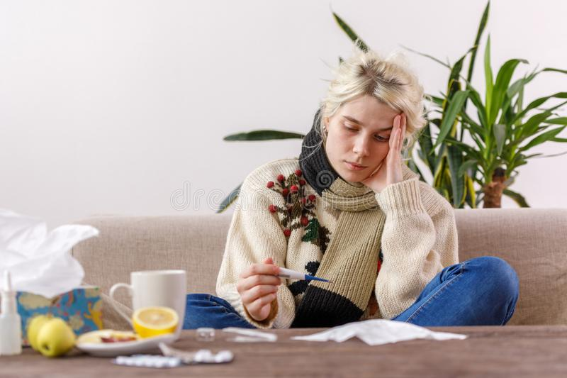 The girl in the sweater is sick sitting on the couch. Colds and flu. The patient caught a cold, feeling sick and looks at a stock images