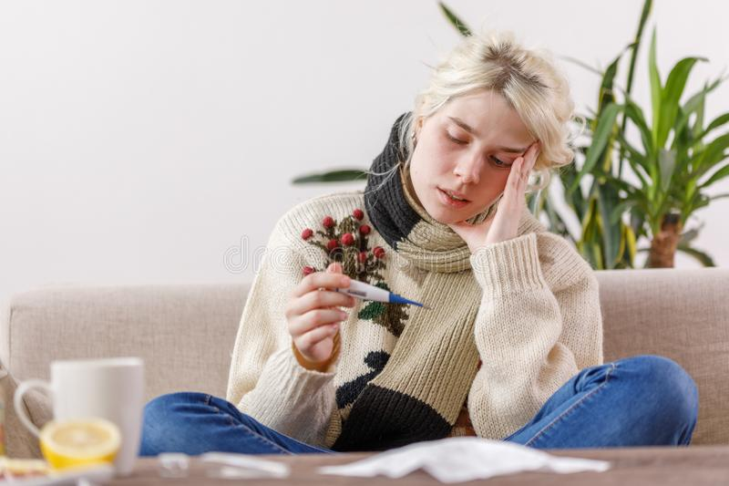 The girl in the sweater is sick sitting on the couch. Colds and flu. The patient caught a cold, feeling sick and looks at a stock photography