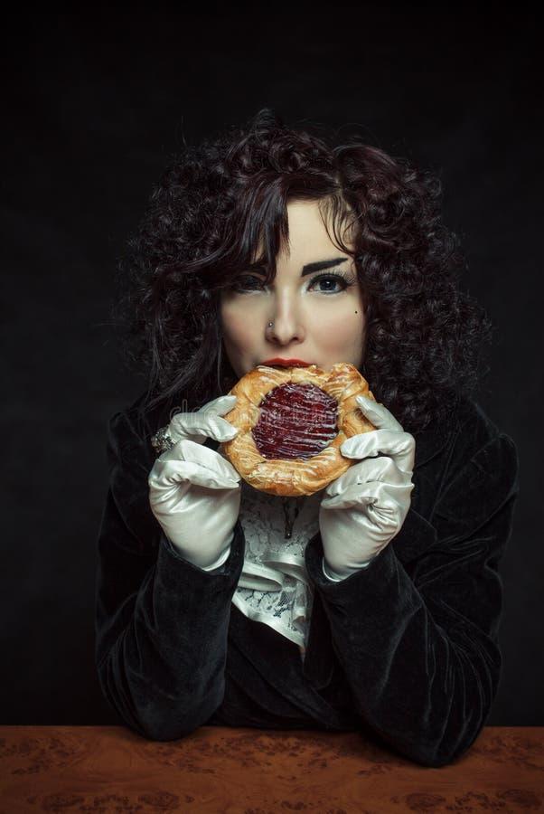 Girl with sweet bun. Gothic girl eating sweet bun over dark background stock photos