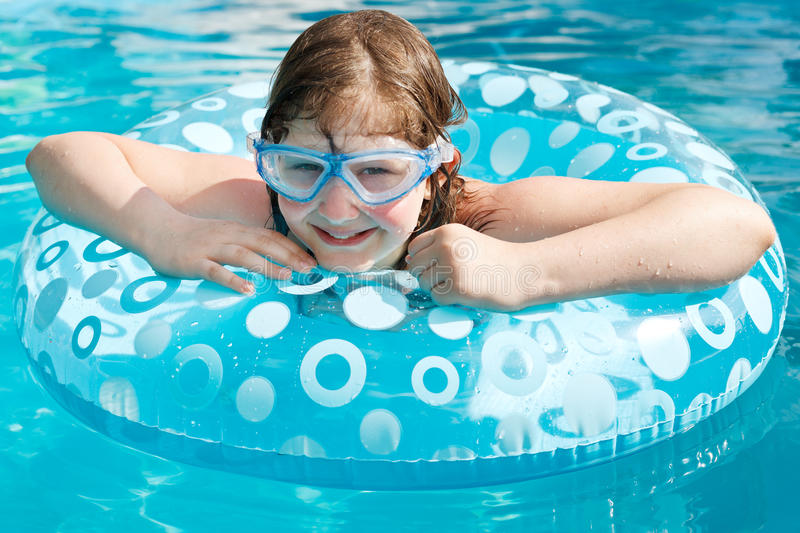 Girl in swim goggle on swimming circle. In blue open-air pool stock photos