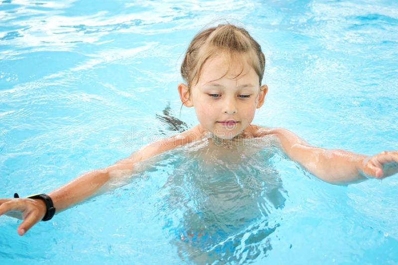 Girl swim in the pool stock photography