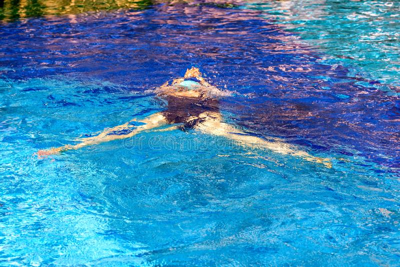 Girl swimmer swims underwater in the pool royalty free stock image