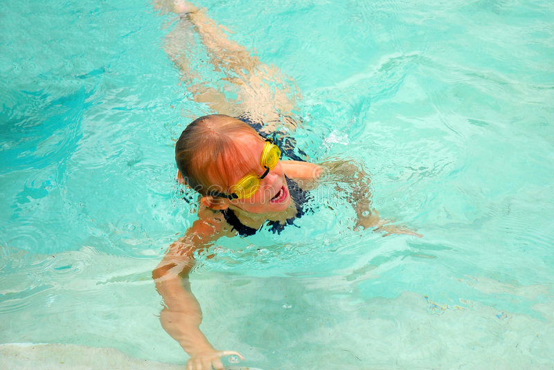 Girl swimming. Outdoor portrait of a cute little blond caucasian girl child with goggles swimming in the water of a pool royalty free stock photo
