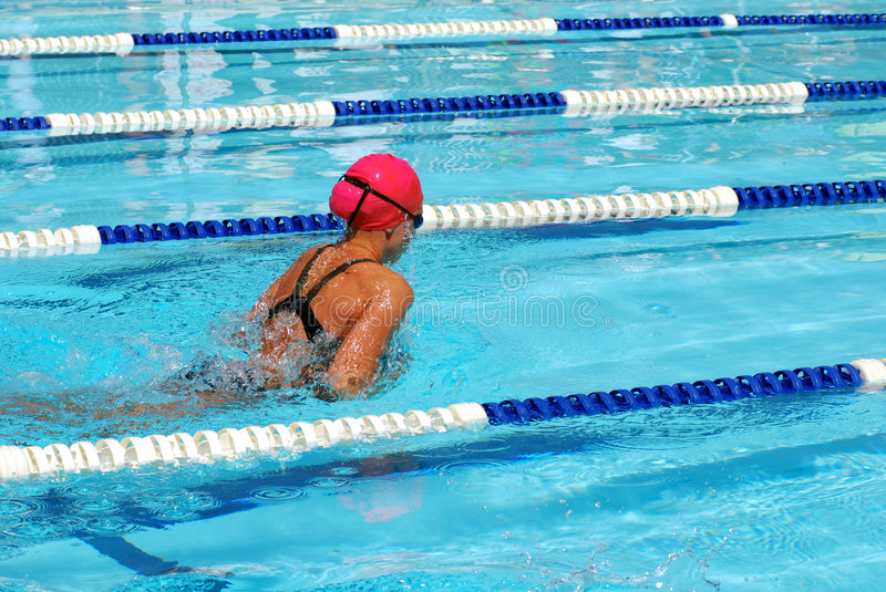 Girl swimming breaststroke. Close-up of young girl in a race swimming breaststroke in the pool with pink swim cap royalty free stock images