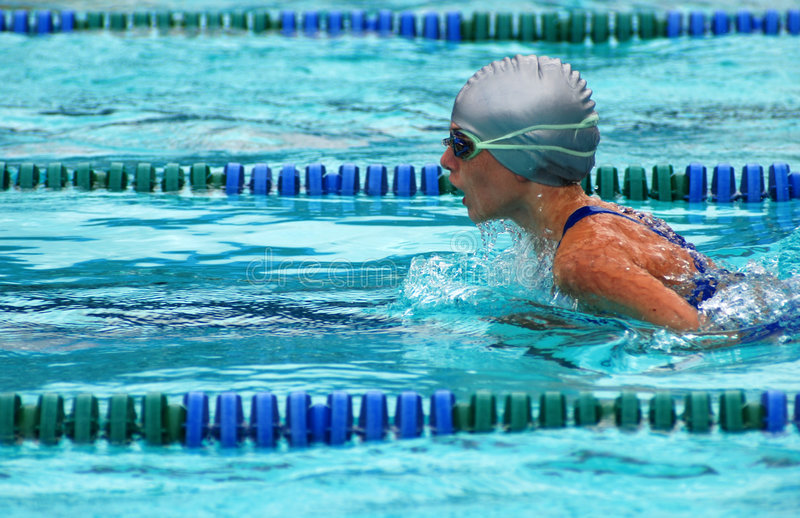 Girl swimming breaststroke. Side view of young girl racing breast stroke event stock photo