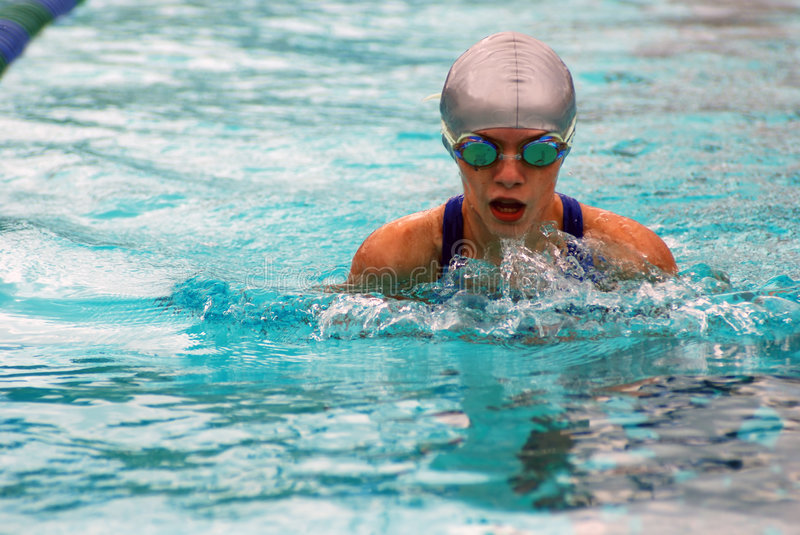 Girl swimming breaststroke. Close-up of young girl in a race swimming breaststroke in the pool with silver swim cap stock images