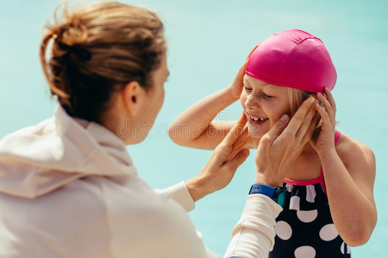 Girl at swimming class. Girl wearing swimming cap by poolside with female trainer in front. Girl getting ready for swimming lessons royalty free stock images
