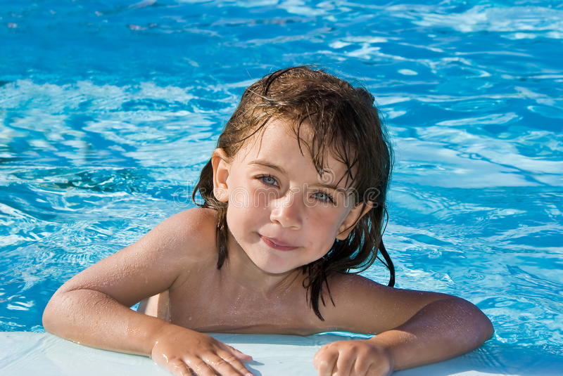 Girl in swimming pool. Girl leaning on the edge of a swimming pool stock photography
