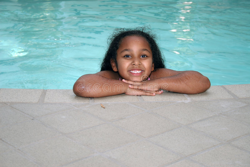 Girl in swimming pool. Smiling multi-racial girl leaning over side of swimming pool stock photo