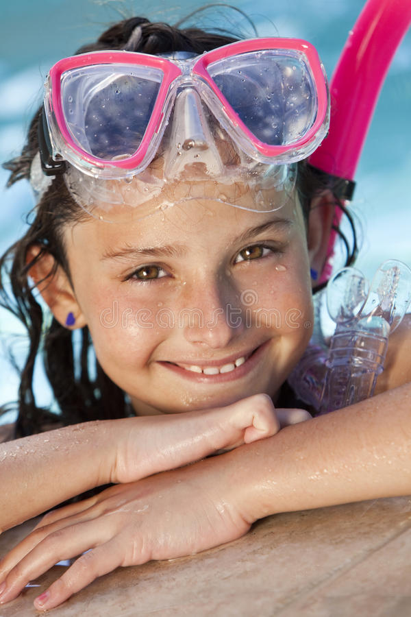 Girl In Swimming Pool with Goggles and Snorkel. A cute happy young girl child relaxing on the side of a swimming pool wearing pink goggles and snorkel stock photo