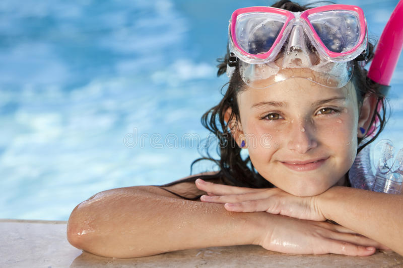 Girl In Swimming Pool with Goggles and Snorkel. A cute happy young girl child relaxing on the side of a swimming pool wearing pink goggles and snorkel royalty free stock image