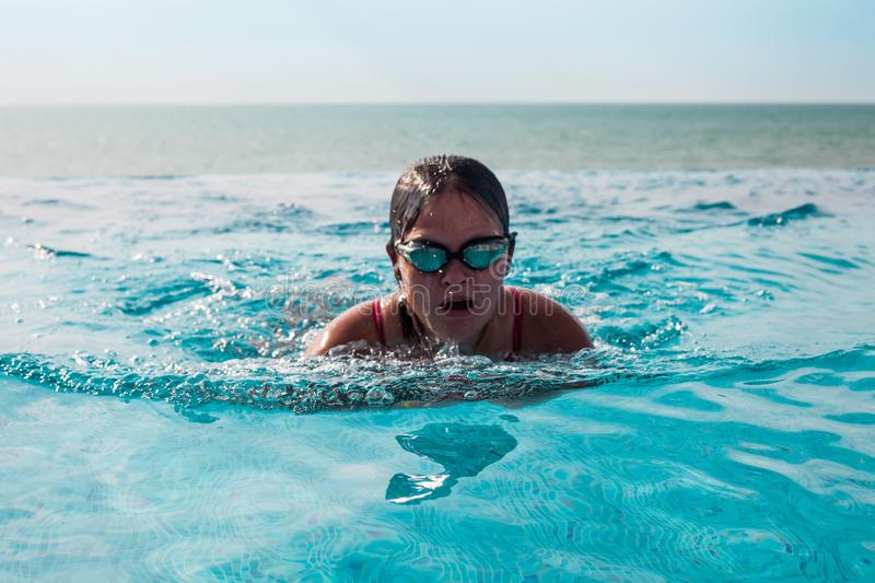 Girl swimming in a pool stock images