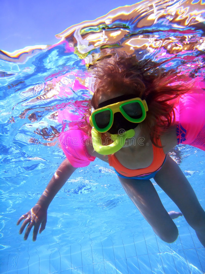 Girl swimming underwater. Young girl in swimming pool