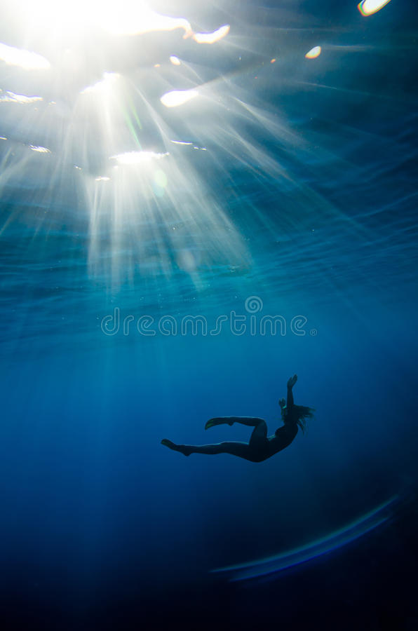 Girl swimming underwater. In a deep blue tropical sea royalty free stock image