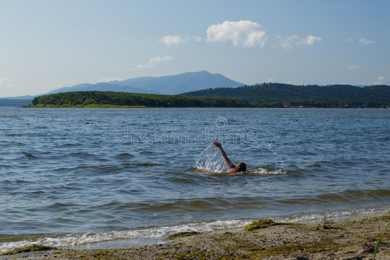 A girl swims in a picturesque lake, spraying water. Motion blur. Tunaycha Lake near the Sunny Beach, Sakhalin Island, Russia, shore, teen, scenic, colorful royalty free stock photo