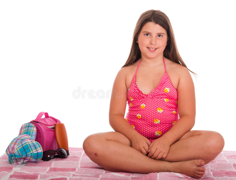 Girl in swimsuit at the beach. Beautiful brunette teenage girl in swimsuit at the beach (studio setting with bag, cap, towel, sun lotion, sunglasses) isolated on stock photos