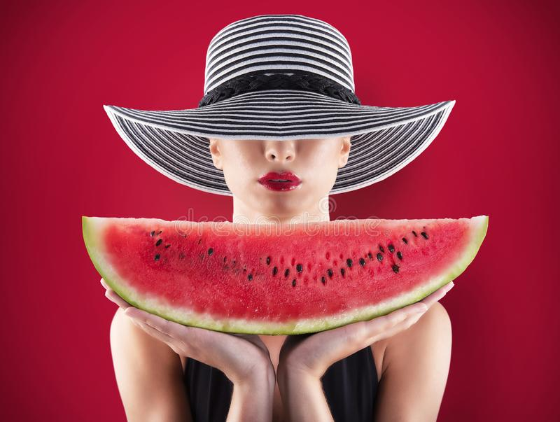 Girl in swimsuit with watermelon in hand and red background stock photos