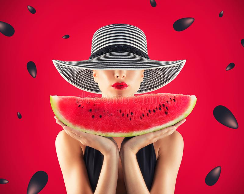 Girl in swimsuit with watermelon in hand and red background with seeds royalty free stock images