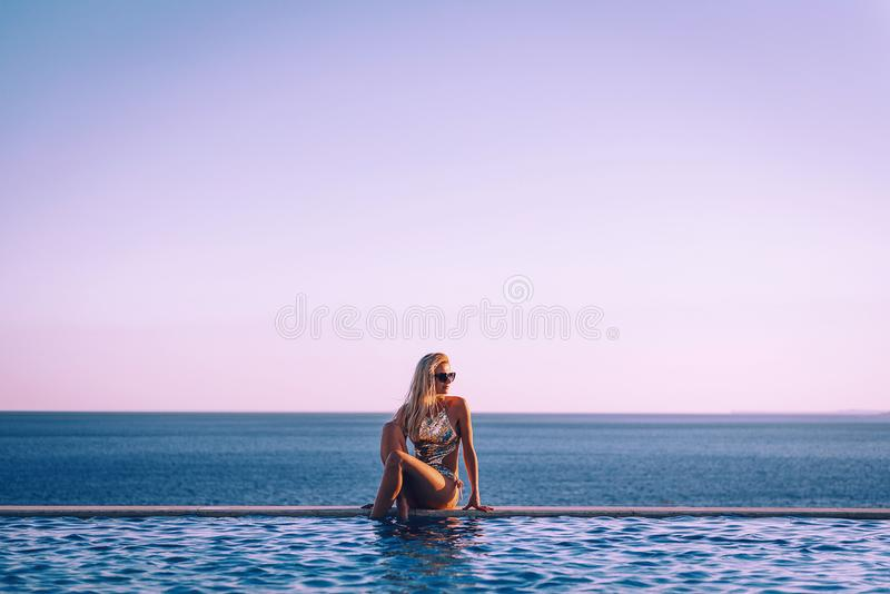 Girl in a swimsuit near the panoramic pool on the background of the sea relaxes royalty free stock photo