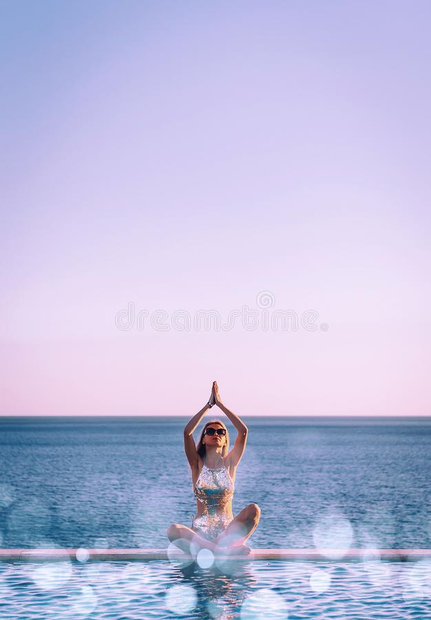 Girl in a swimsuit near the panoramic pool on the background of the sea relaxes stock photos