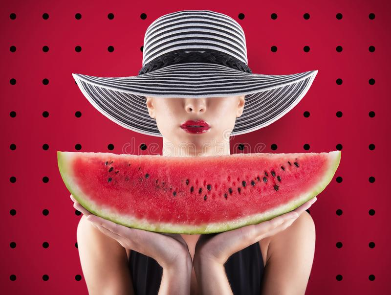 Girl in swimsuit with watermelon in hand and red background royalty free stock photos