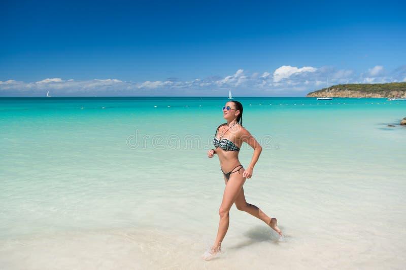 Girl swimwear bikini run wave azure ocean beach. Vacation luxury tropic ocean beach resort. Run through magical stock images