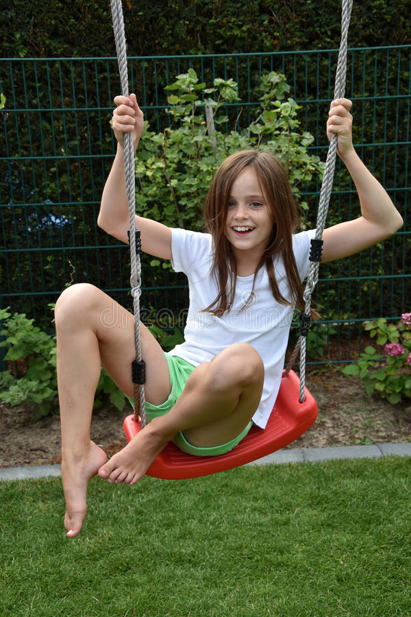 Girl on swing. Cute teenager girl on swing stock photography