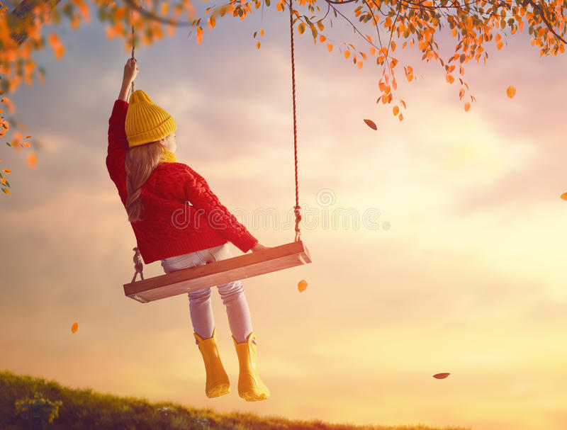Girl on swing. Happy child girl on swing in sunset fall. Little kid playing in the autumn on the nature walk royalty free stock photos