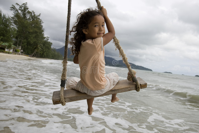 Girl on swing at the sea stock photo