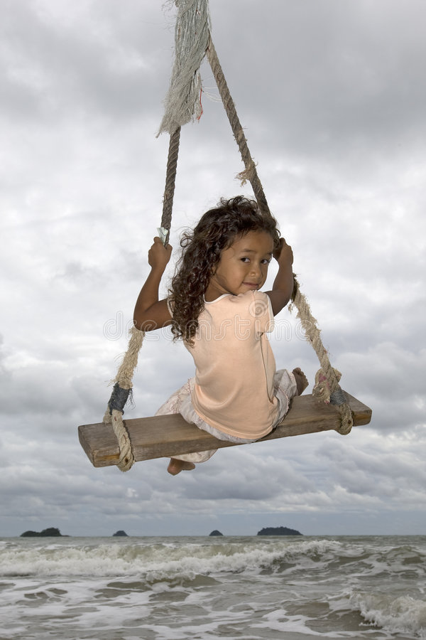 Girl on swing at the sea royalty free stock photos