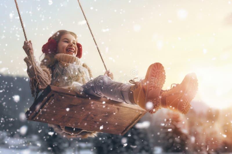 Girl on swing in sunset winter stock images
